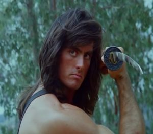 A white guy with long hair weilding a Katana, an image so 90's you can taste it.
